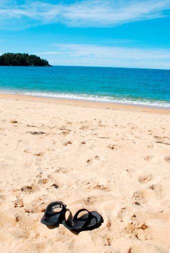 New Zealand Culture「Flip flops in the sandy beach before the bright blue water」:スマホ壁紙(18)