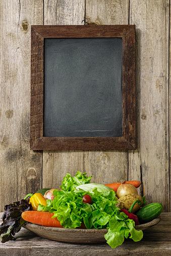 ニンジン「古い木の板壁に掛かっている木製の組み立てられた空白黒板の下にある古い木製のボウルでサラダ野菜。」:スマホ壁紙(0)