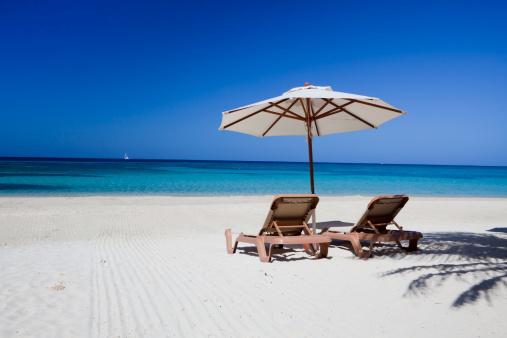 Roatan「Two lounge chairs lying on a clear beach under a parasol」:スマホ壁紙(12)
