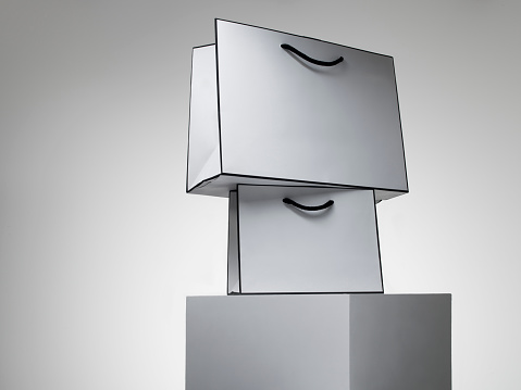 Spending Money「A series of white shopping bags stacked on a white plinth against a grey background」:スマホ壁紙(16)
