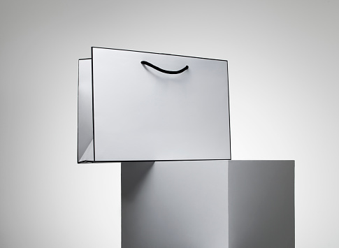 Gray Background「A series of white shopping bags stacked on a white plinth against a grey background」:スマホ壁紙(6)