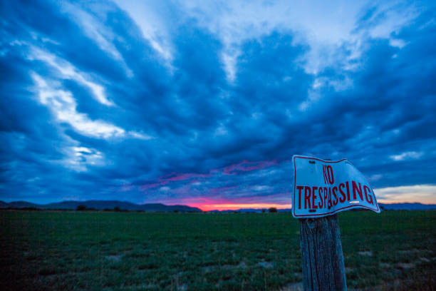 No trespassing sign under clouds at sunset:スマホ壁紙(壁紙.com)