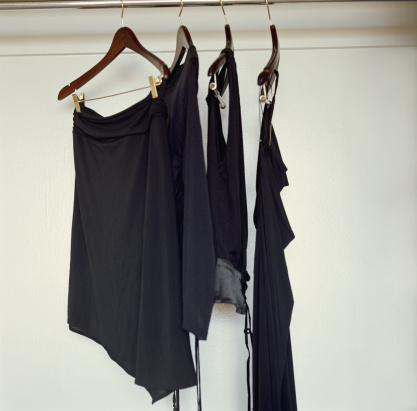 Skirt「Black clothing hanging from hangers in closet」:スマホ壁紙(11)