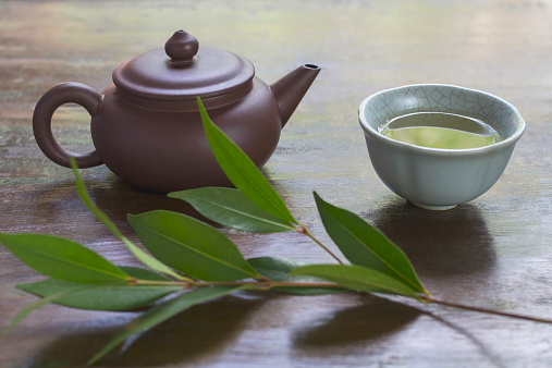 Teapot「Still life with ceramic teapot, cup of green tea, and branch of tea plant」:スマホ壁紙(7)