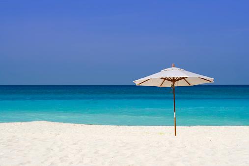 Sunshade「A parasol in the sand at a beach」:スマホ壁紙(1)