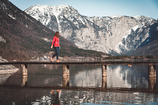 Dachstein Mountains「Women in a red jacket walking on a tiny bridge over the lake」:スマホ壁紙(19)