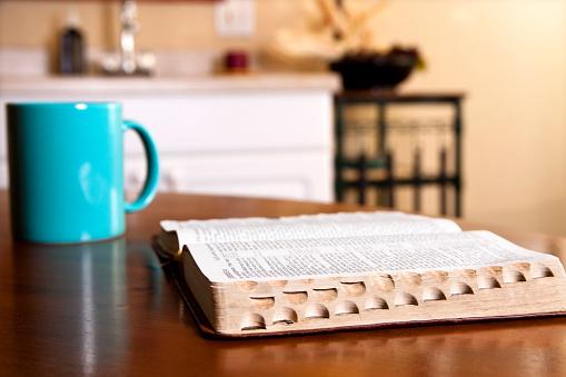Spirituality「Open Bible on kitchen table with coffee mug」:スマホ壁紙(0)