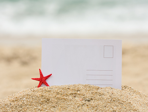 Souvenir「Blank postcard stuck in mound of sand next to a starfish」:スマホ壁紙(14)