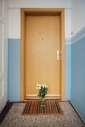 Care「Vase with bunch of white farewell flowers on floor mat at apartment door of deceased neighbour」:スマホ壁紙(7)