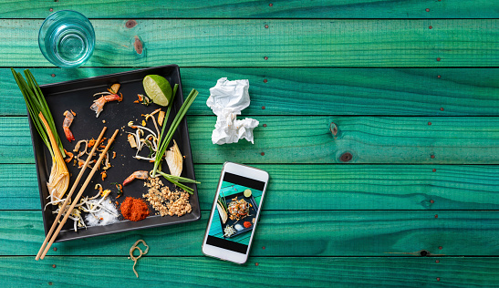 PGA Event「Empty messy plate of just eaten delicious Thai Prawn Pad Thai noodles with chopsticks left on the plate, with a smartphone next to it showing the meal before it was eaten, set on an old wooden panel turquoise colored table background.」:スマホ壁紙(6)