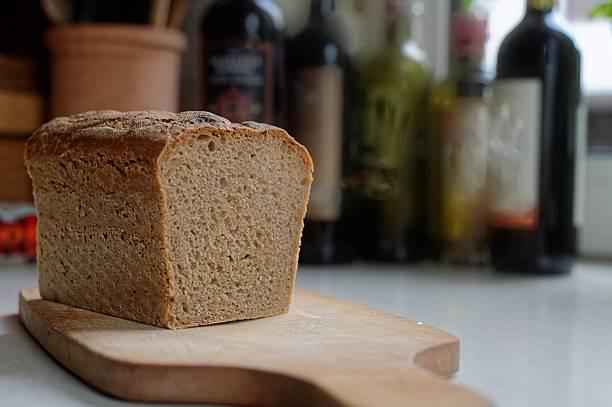 A loaf of homemade sourdough bread on a chopping board:スマホ壁紙(壁紙.com)