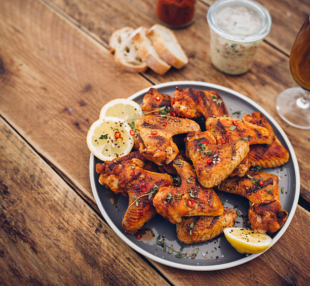 Plate of spicy chicken wings on a wooden table:スマホ壁紙(壁紙.com)