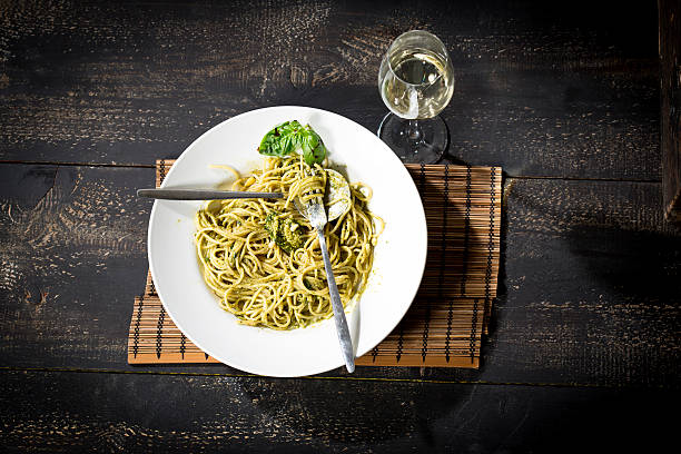 Plate of spaghetti with pesto Genovese and glass of white wine:スマホ壁紙(壁紙.com)