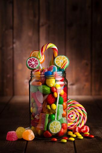 グミ・キャンディー「素朴な木製のテーブルの上のキャンデーの瓶」:スマホ壁紙(16)