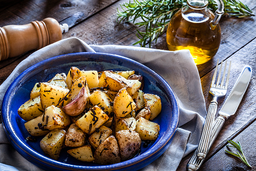 Vegetarian Food「Roasted potatoes in a blue plate on wooden kitchen table」:スマホ壁紙(13)