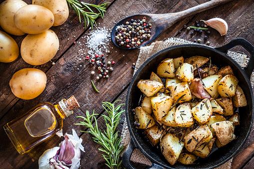 Cast Iron「Roasted potatoes on wooden kitchen table」:スマホ壁紙(12)