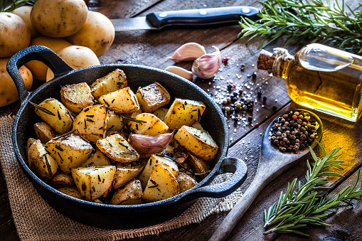 Cast Iron「Roasted potatoes on wooden kitchen table」:スマホ壁紙(2)