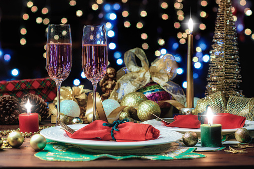 Glitter「Shot of Champagne flutes in table for two over golden holiday background. Christmas and New Year celebration」:スマホ壁紙(15)