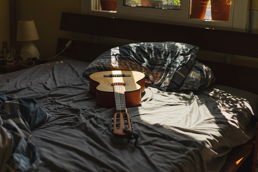 Guitar「Acoustic guitaron top of a bed with sunlight coming through the window」:スマホ壁紙(1)