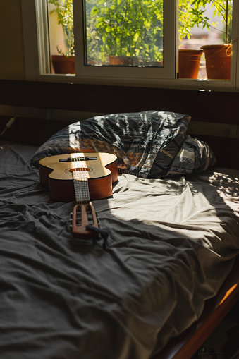 Guitar「Acoustic guitaron top of a bed with sunlight coming through the window」:スマホ壁紙(6)