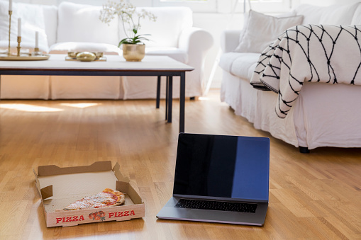 Pizza Box「Pizza box with pizza and laptop standing on floor of living room」:スマホ壁紙(4)
