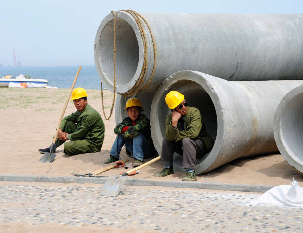 Workers resting during the laying of an outlet pipe to the sea, Shanhaiguan, Hebei province, China:ニュース(壁紙.com)