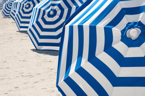 鮮やかなブルーとホワイトのストライプのビーチパラソルの列:スマホ壁紙(壁紙.com)
