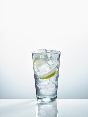 Cold Temperature「Glass with mineral water, ice cubes and slices of lemon in front of white background」:スマホ壁紙(16)
