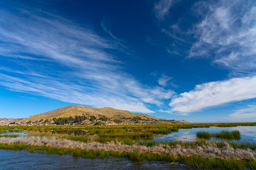 Peru「Dramatic cloudscape and blue sky above reed marshes at Puno, Lake Titicaca, Peru」:スマホ壁紙(4)