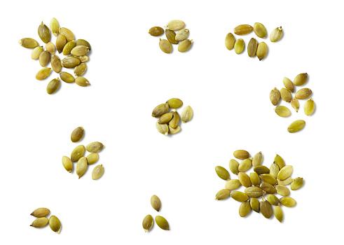 Seed「Overhead piles of pumpkin seeds on white surface」:スマホ壁紙(8)