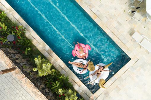若い女性「スイミング プール - 空撮で膨脹可能なフロートを楽しんで友人」:スマホ壁紙(0)