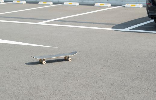 Motorized Vehicle Riding「A skateboard rolling in a parking lot.」:スマホ壁紙(5)