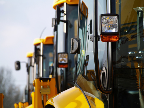 Construction Vehicle「Diggers in a Row on Industrial Parking Lot」:スマホ壁紙(0)