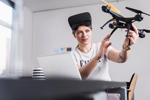 白人「Young woman with laptop and VR glasses at desk holding drone」:スマホ壁紙(8)