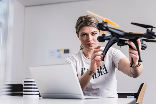 女性一人「Young woman with laptop at desk holding drone」:スマホ壁紙(4)