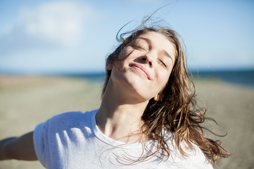 Serene People「Young woman with eyes closed smiling on a beach」:スマホ壁紙(1)