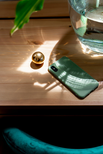 Mobile Phone「Mobile phone by golden ball on wooden desk in bedroom at home」:スマホ壁紙(12)