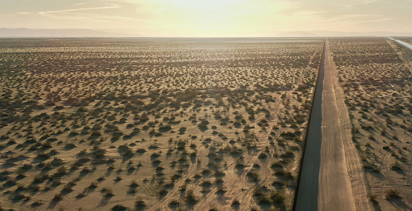 Mexico「Aerial Drone Shot of a Dirt Road Running Parallel to the Steel-Slat Border Wall between Mexico and the United States on a Sunny Afternoon in the California/Mexican Desert with Distant Mountains in the Background」:スマホ壁紙(2)