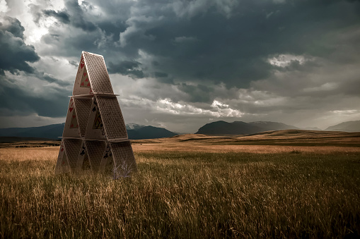 Uncertainty「Playing cards set up in a grass field under a stormy sky, composite image」:スマホ壁紙(5)