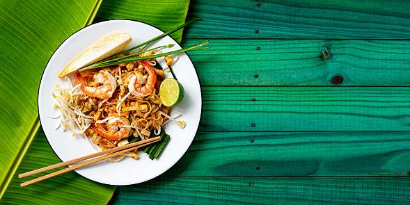 Nut - Food「World famous Thai recipe of Prawn Pad Thai noodles with chopsticks on a dish and banana leaf on a turquoise colored old wood panel table background.」:スマホ壁紙(2)
