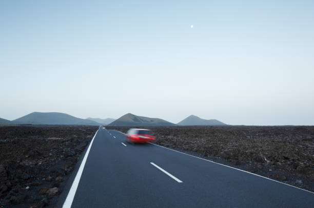 Red car in blurred motion travelling on straight road crossing lava plains towards distant volcanoes.:スマホ壁紙(壁紙.com)