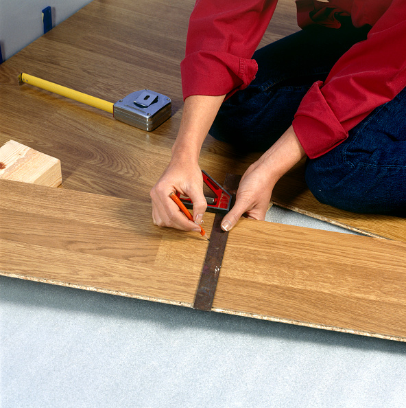 Flooring「Woman laying new laminated floorboard」:写真・画像(16)[壁紙.com]