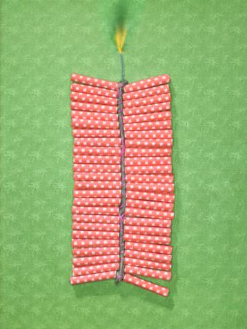 花火「String of  firecrackers with lit fuse on green patterned paper」:スマホ壁紙(11)
