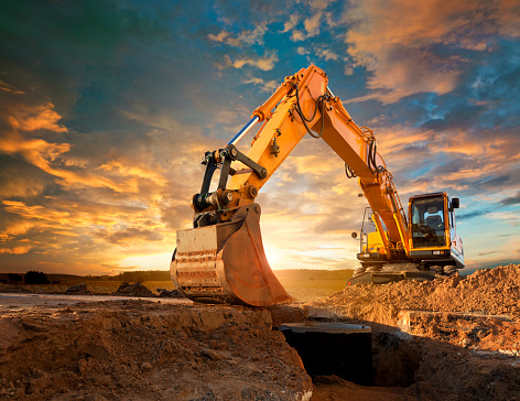 Construction Vehicle「Excavator at a construction site against the setting sun.」:スマホ壁紙(0)