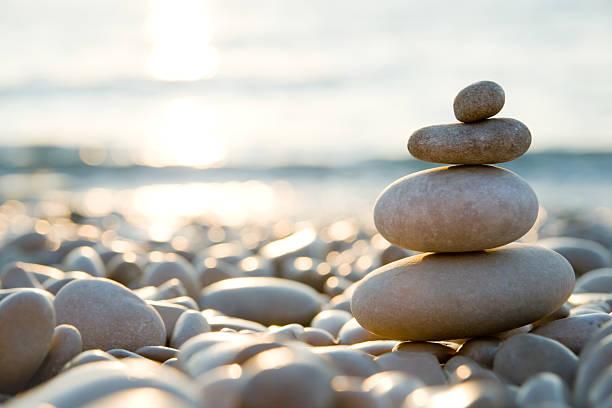 Balanced stones on a pebble beach during sunset.:スマホ壁紙(壁紙.com)
