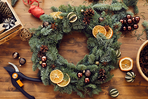 Branch - Plant Part「High angle view of beautiful holiday wreath decorated orange slices, fir tree cones and small balls placed on wooden table among decorations and tools」:スマホ壁紙(3)