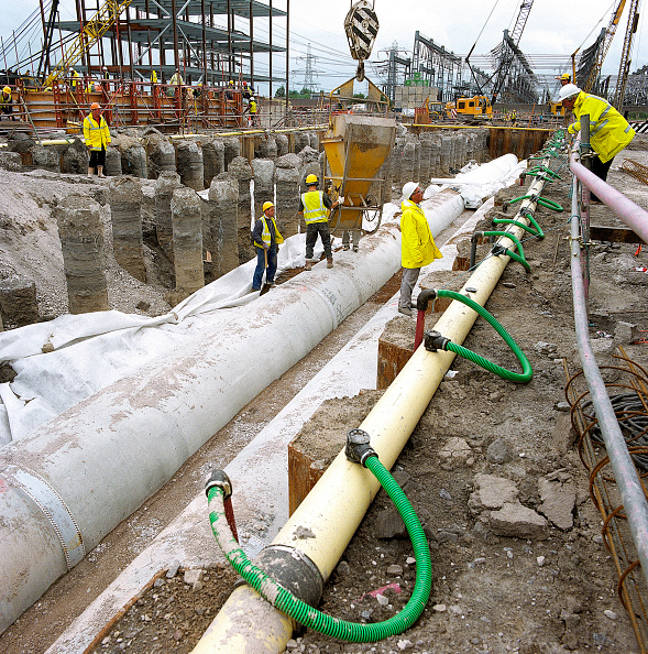 Pouring「Pouring concrete from hopper to haunch of precast concrete pipes. Dewatering system (green pipes) in operation to remove groundwater during construction. Connahs Quay gas-fired power station, North Wales, United Kingdom.」:写真・画像(0)[壁紙.com]