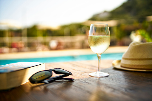 Wineglass「Glass  of cooles white wine, book, sunglasses and straw hat in  front of swimming pool, Italy」:スマホ壁紙(7)