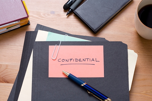 File「Black confidential files on a wooden desk with stationery」:スマホ壁紙(4)
