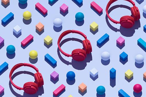 斜めから見た図「Three red wireless headphones surrounded by geometric shapes, 3D Rendering」:スマホ壁紙(1)